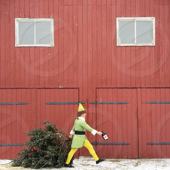 person in green and yellow elf costume holding a jug and walking past a red building photo