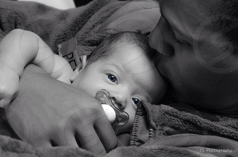 A father seeing his beautiful blue-eyed baby after deployment.  photo