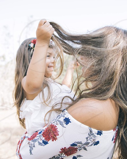 woman with brunette hair in white red and blue off shoulder floral top carrying girl with brunette hair in white ruffle top photo
