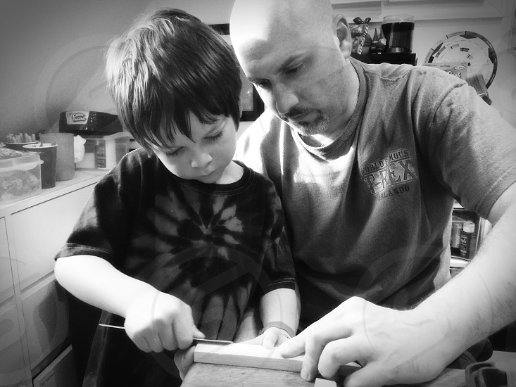 Father and son working together to build a little wooden boat.  photo