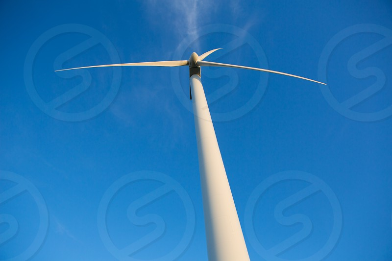 Aerogenerator windmills for green electric energy from below and ble sky background photo