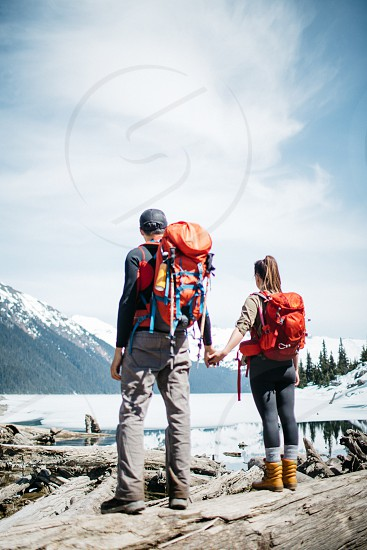 couple holding hands while standing on grey rocky mountain top over looking a frozen lake under blue sky with white clouds during daytime photo