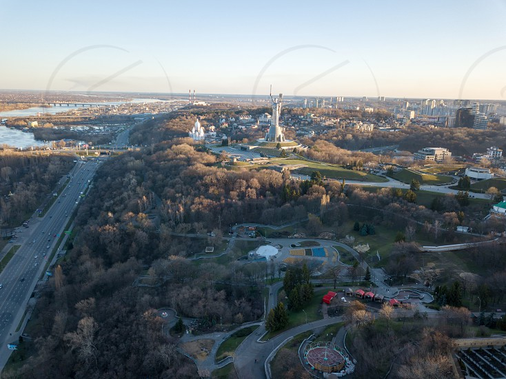 Aerial view from the drone to the Dnieper River the Motherland Monument Spivoche Pole parks historical and modern architecture of city in Kiev Ukraine in the summer sunset. photo