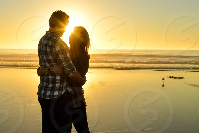 man and woman hugging under yellow sunset photo