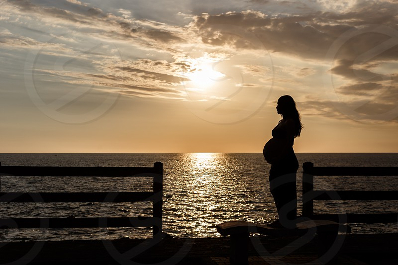 Silhouette shot of a pregnant woman against a sunset sky over the ocean.  photo