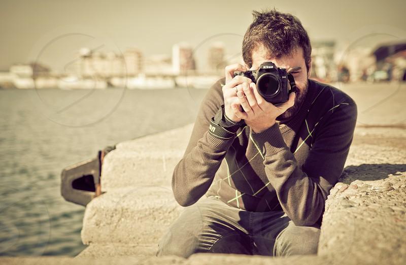 man taking photo using black nikon dslr camera photo