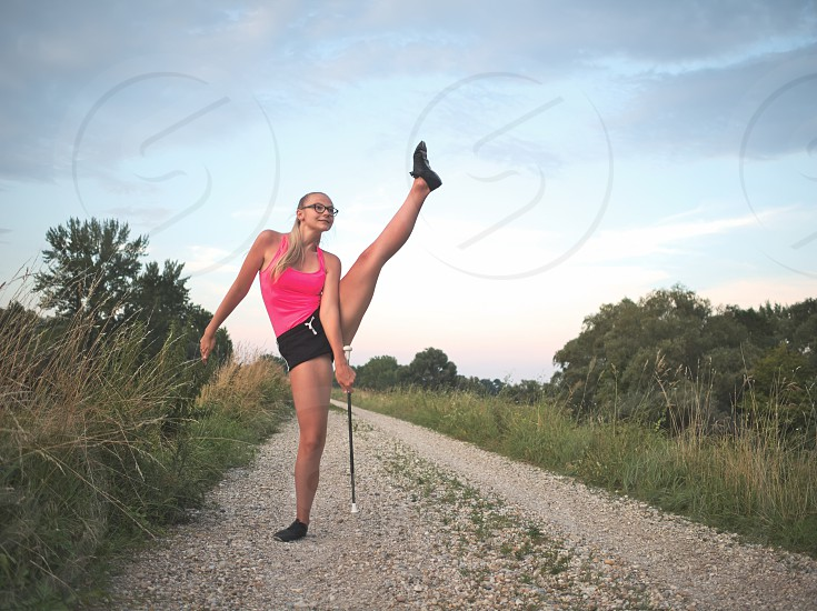 Bespectacled Blonde Teen Majorette Girl Twirling Baton Outdoors in Workout Clothing photo