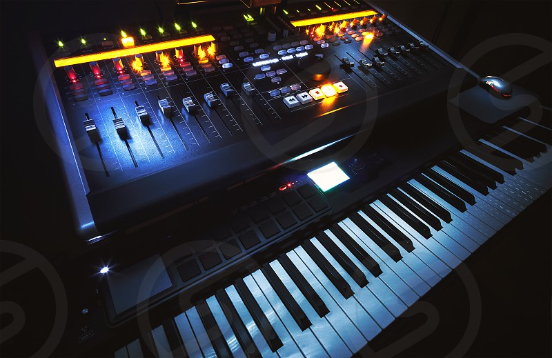 Closeup view on small modern home music studio keyboard mixing console and computer.  photo