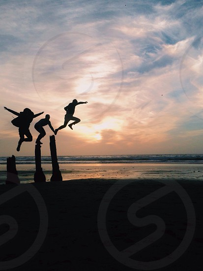 people jumping silhouette on sunset photo