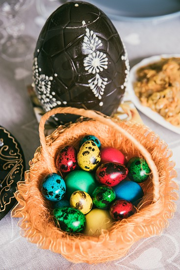 Colourful Easter eggs in the basket and huge decorated chocolate egg besides photo
