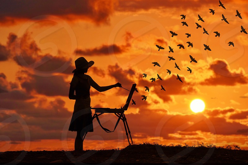 silhouetted of a woman painting a flock over birds flying over a mountain on canvas during orange sunset photo