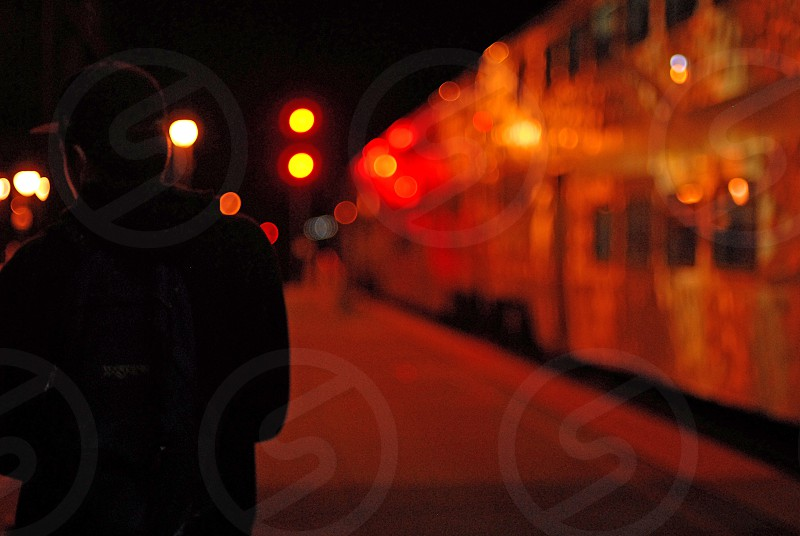Silhouette at a railroad station lit up with lamps at night  photo