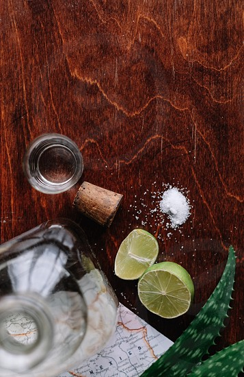 glass tequila bottle with halved limes salt and a shot glass on a wood table photo