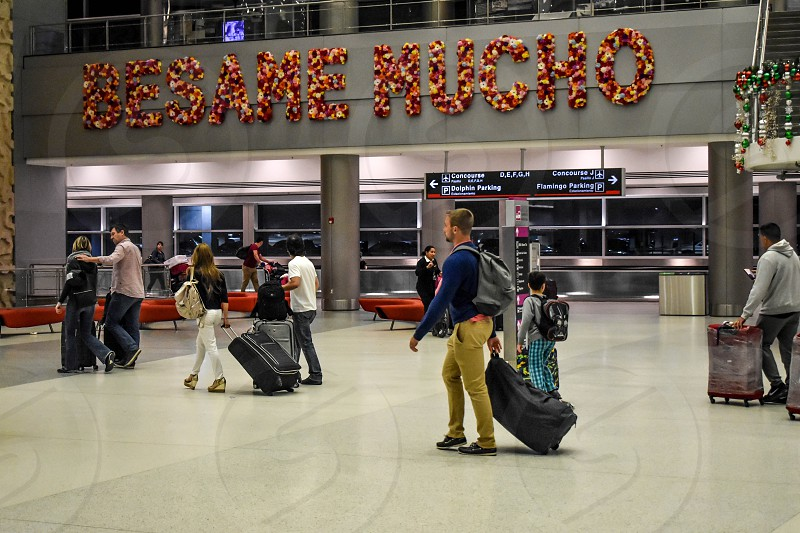 Miami Florida. January 05 2019. People walking with suitcases and Besame Mucho flower sign  at Miami International Airport . photo