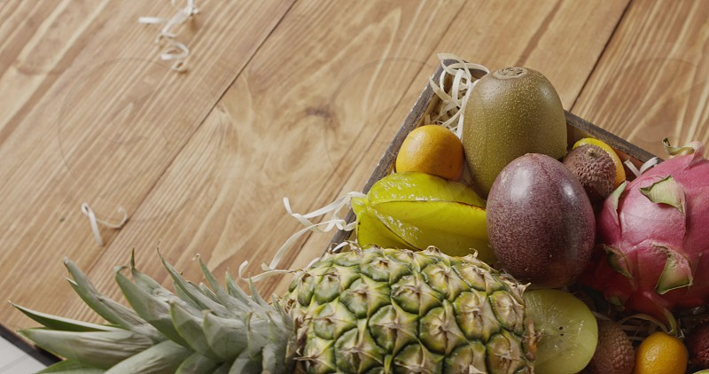 Juicy pineapple dragon fruit passion kiwi in a box on a wooden background. Top view. Panoramic motion 4K UHD video 3840 2160p. Top view. photo