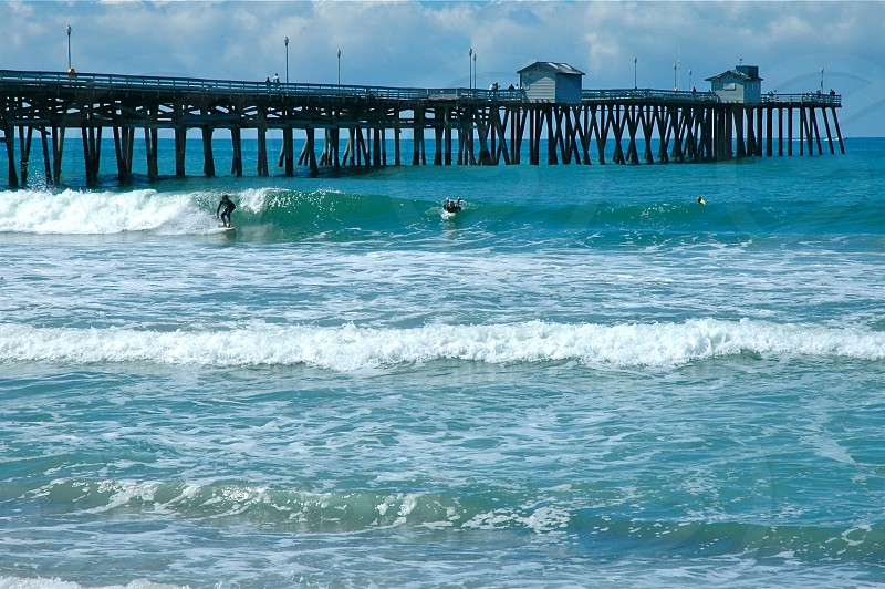 person surfing on blue sea beside wooden dock under white cloudy sky during daytime photo