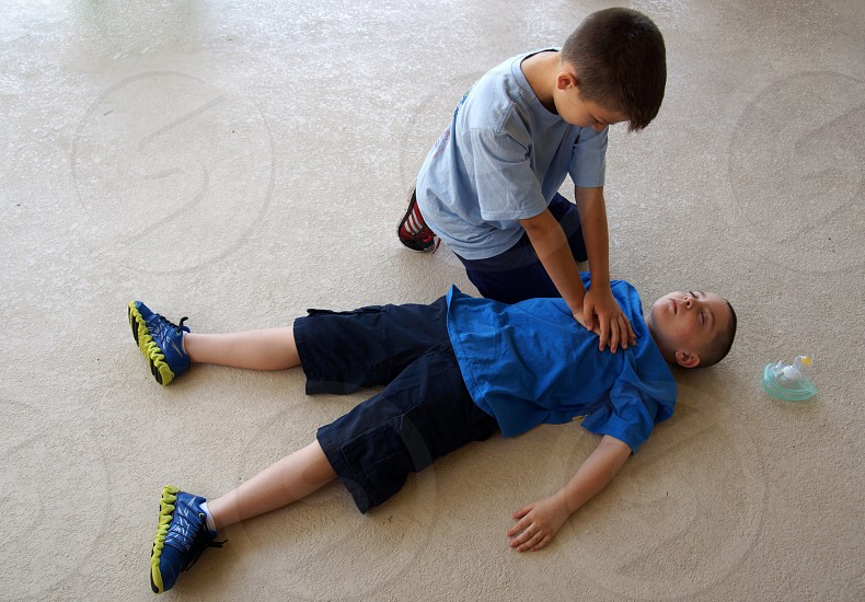 boy performing a cpr on the other boy photo