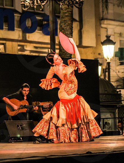 woman in white red and brown floral tiered skirt poet sleeve traditional dress holding a red hand fan while performing a dance presentation near a man playing guitar photo