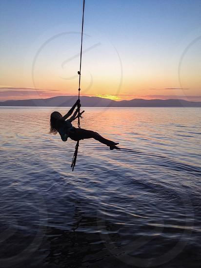 Swing girl sunset lake photo