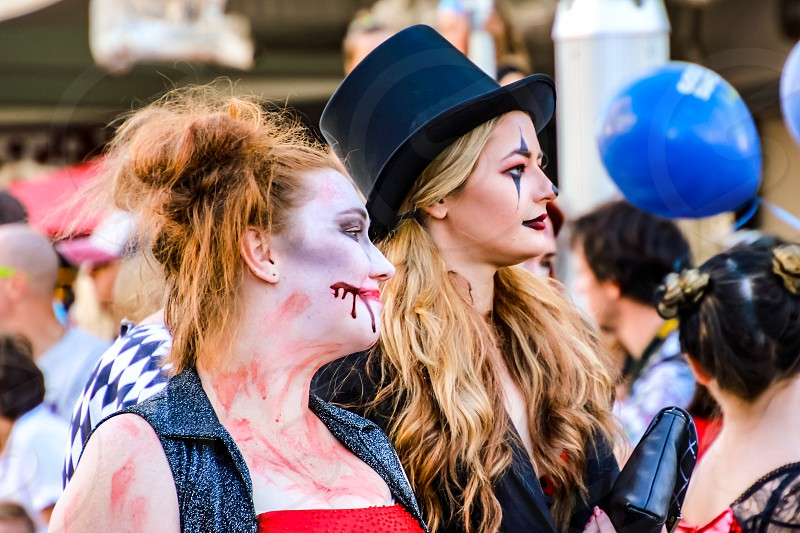 young girls in costume at a street parade face paint Halloween fun photo