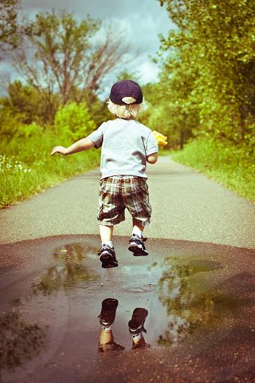 Child Youth Jumping Play Toy Rake Summer Splash Puddle Water Shorts Blonde Boy Shoes Trail Path Walk Fun photo