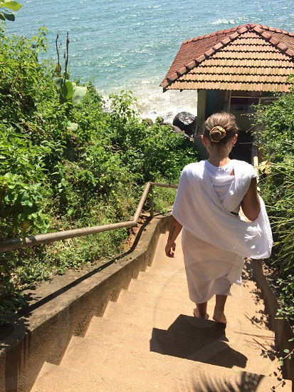 blonde haired woman in white dress walking down brown staircase between green leafed plants during daytime photo