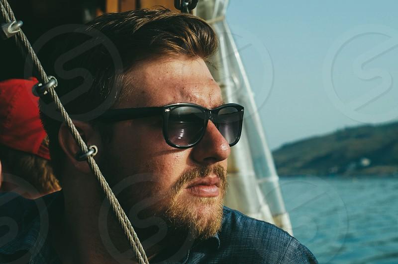 macro photography of man in black wayfarer sunglasses and black top near body of water photo
