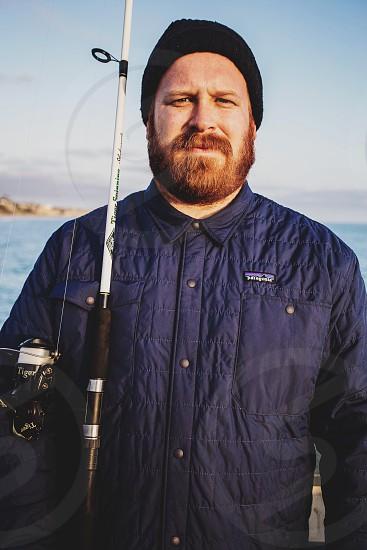 man in blue jacket holding black white fishing rod photo