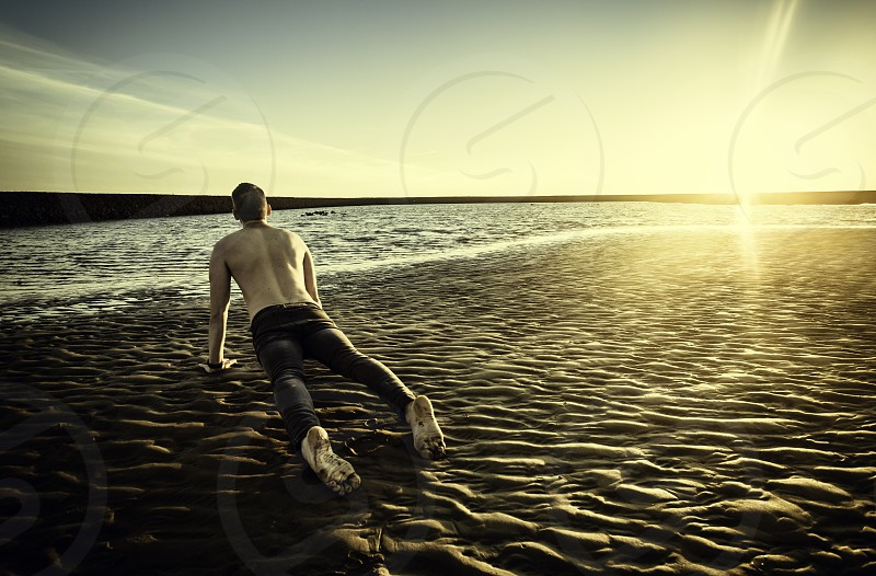 Young man doing yoga in the sand of the beach of Sanlucar de Barrameda at sunset when the tide is low photo