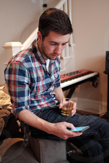 man in plaid shirt and jeans with drink looking at phone on arm of sofa photo