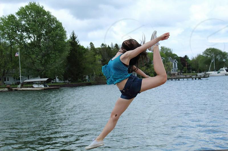 woman acrobat near lake photography during daytime photo