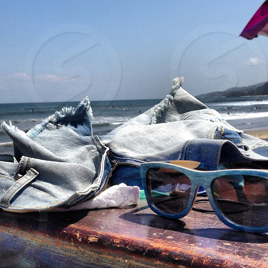 Shorts and wooden frame sunglasses at the beach photo