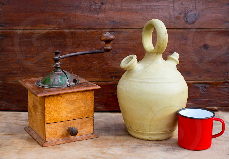 retro old coffee grinder with vintage botijo clay jar on aged wood photo
