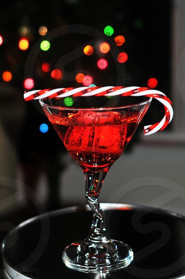 Festive red holiday Christmas cocktail martini with a candy cane photo