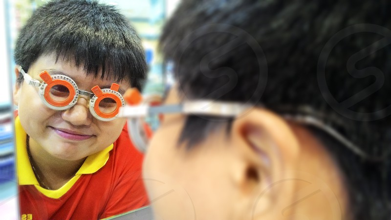 Closeup portrait of a happy Asian boy wearing trial frame eyeglasses photo