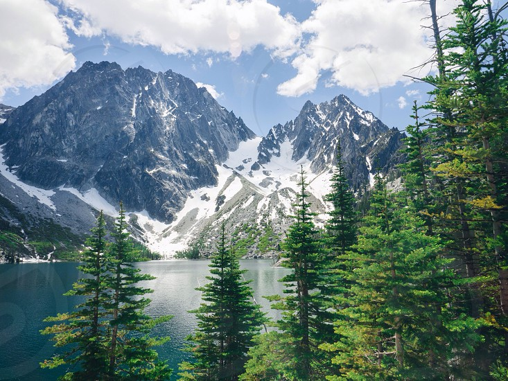 white snowy mountains pine trees white clouds and blue lake photo