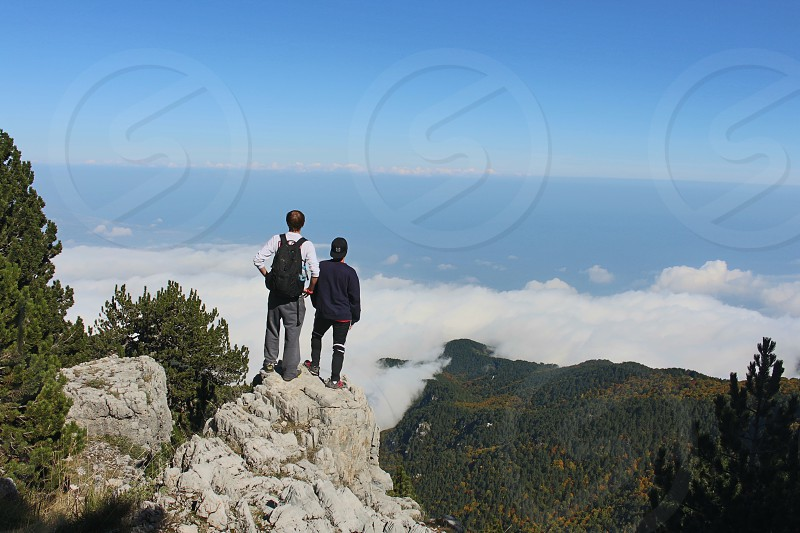 2 person standing on gray rocky ledge on mountain top with overlooking view of green forest during daytime photo