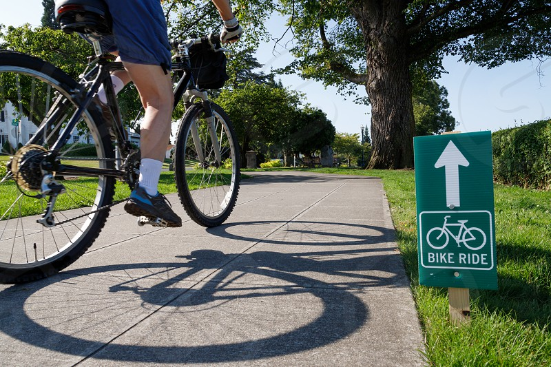 Bike Ride Sign along bicycle path with rider photo