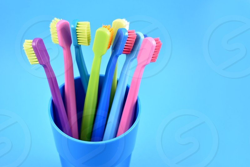 Colored toothbrushes. Morning hygiene. Bathroom accessories images. Toothbrush on a blue background. Toothbrush on a blue background with copy space for text photo