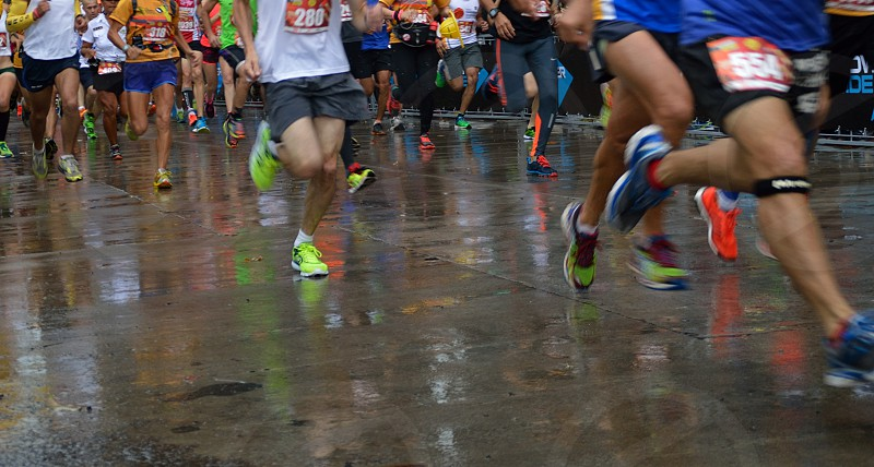 group of people in running shoes running on wet pavement during marathon photo