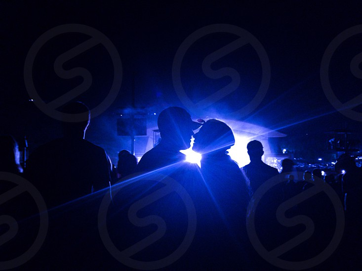 people standing near white lights on concert stage under night sky photo