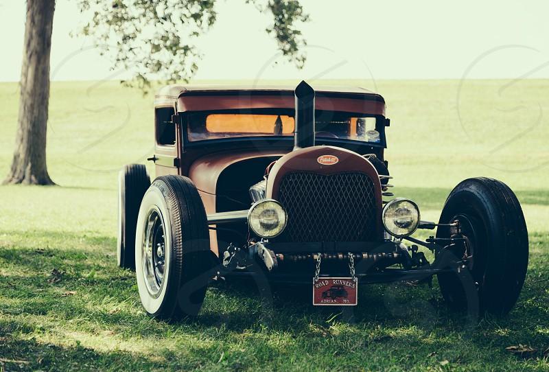 vintage roadster parked under tree photo
