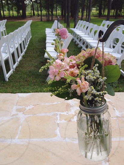 Pink Flowers in Glass Mason Jar Near White Chairs photo