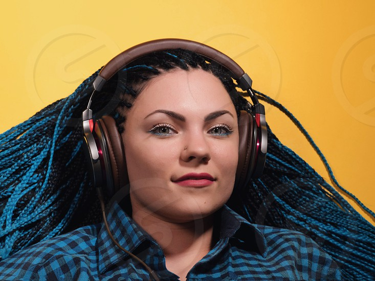 Beautiful young girl with african blue braids is listening to music with headphones and dancing. Woman on bright yellow background. Dyed Hair moves. photo