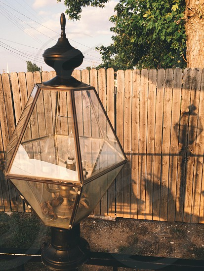 black metal lamp post and brown wooden fence photo