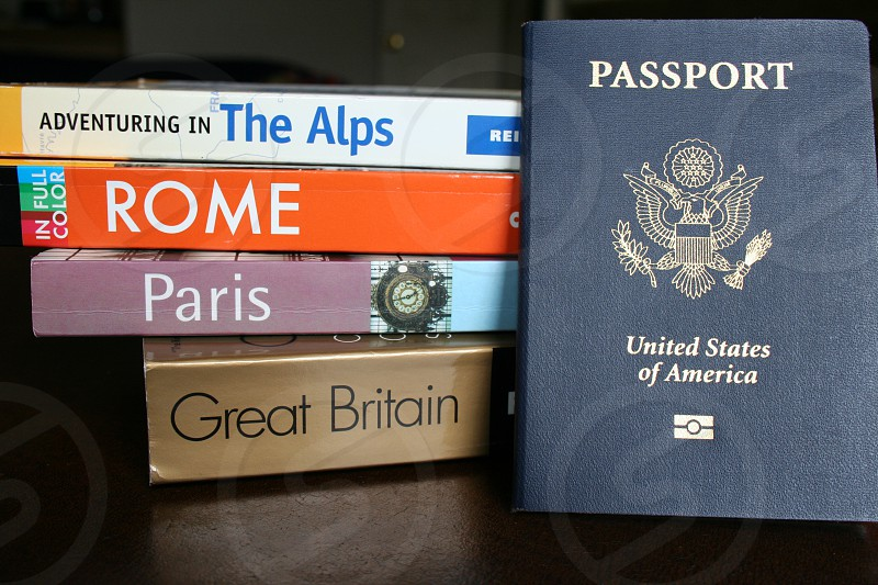 united states of america passport in front of adventuring in the alps in full color rome paris and great britain books photo