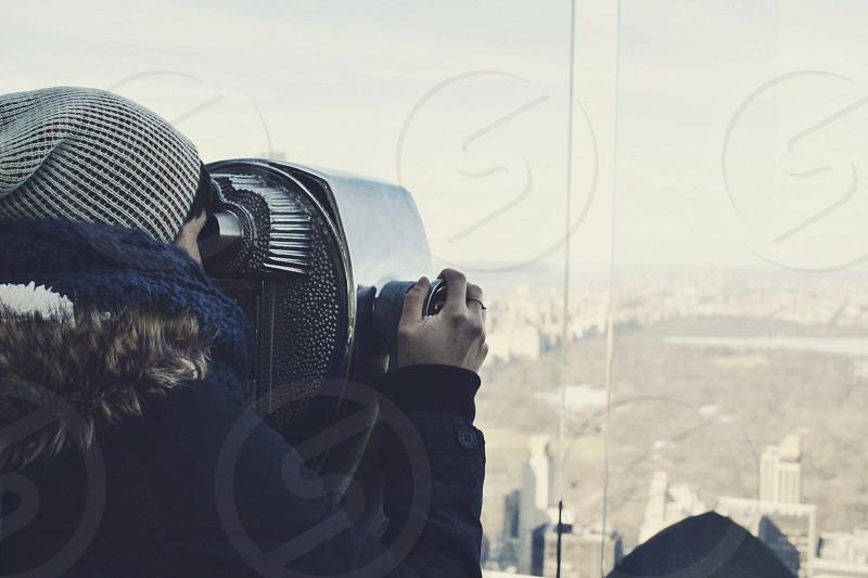 person looking through coin slot binoculars  photo