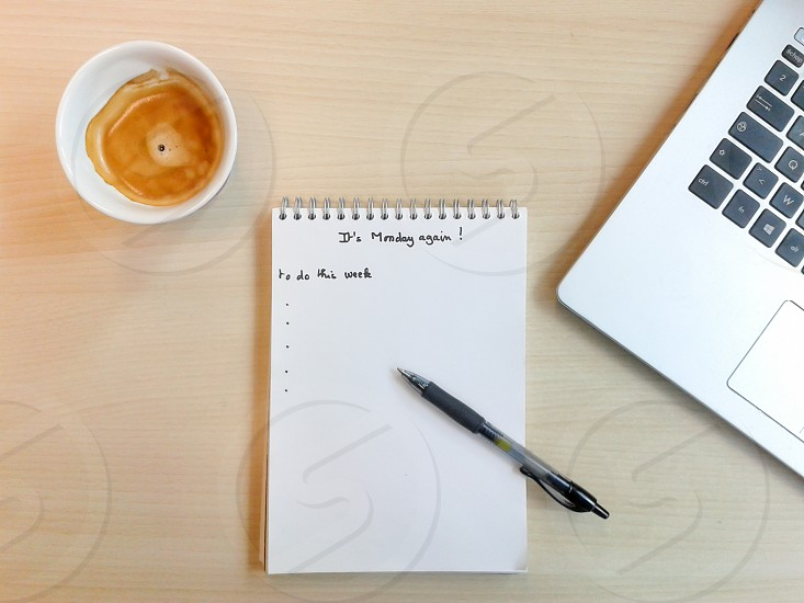 It's Monday again ! A notepad a much needed coffee a pen a note pad a laptop and almost ready for another week ! photo