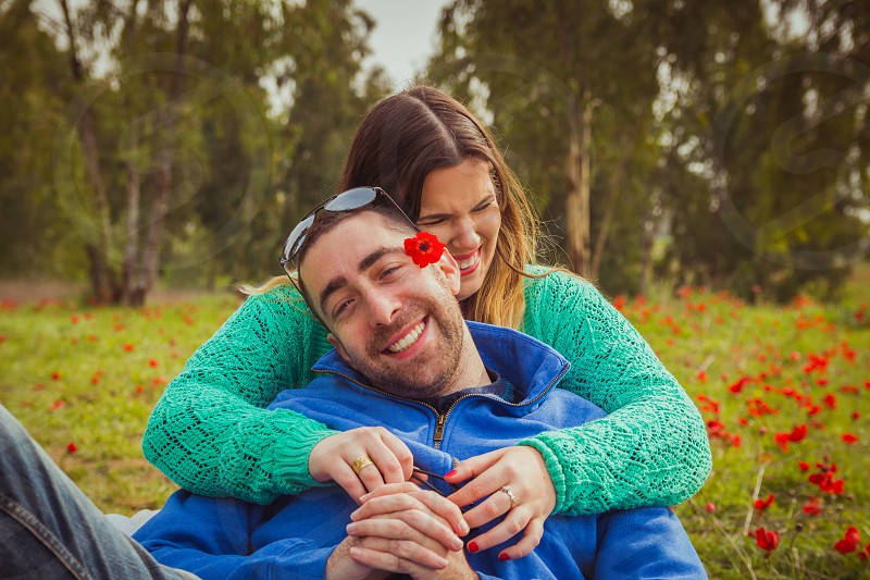 Young couple sitting on the grass in a field of red poppies and smiling and laughing at each other photo