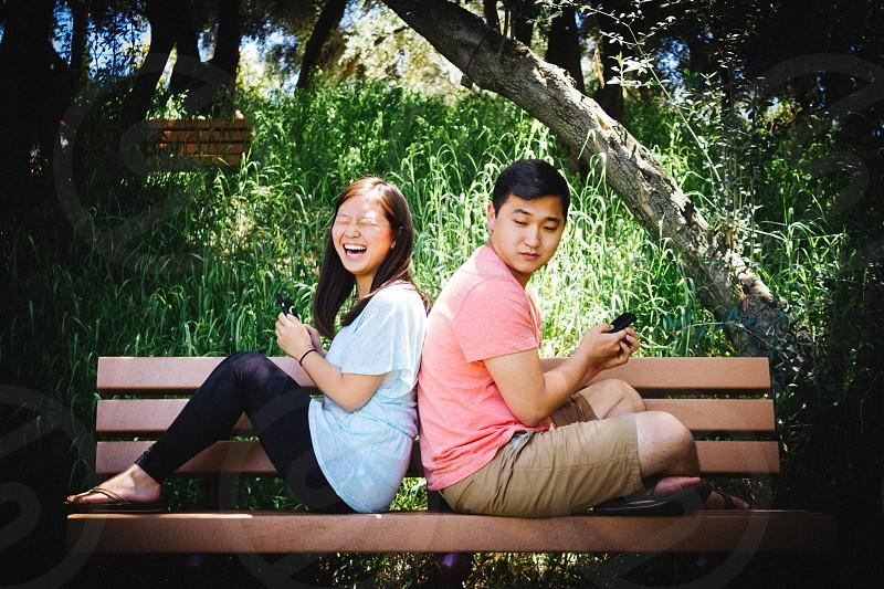 man in pink t shirt sitting on bench beside woman in black leggings laughing photo